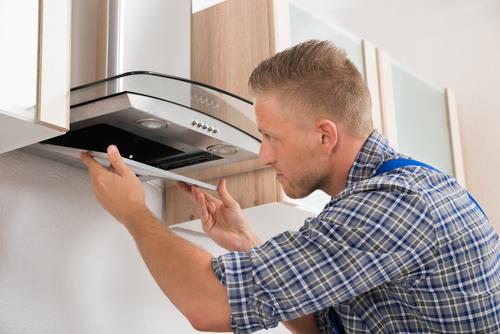 мастер ремонтирует вентиляцию кухни