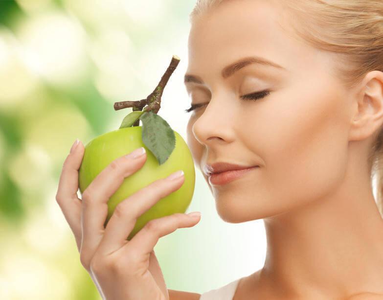 Женщина нюхает яблоко